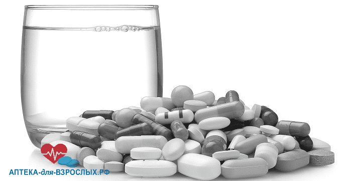 Стакан воды с капсулами и таблетками
