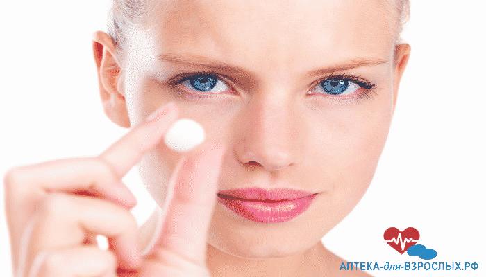 Голубоглазая девушка держит в руке таблетку