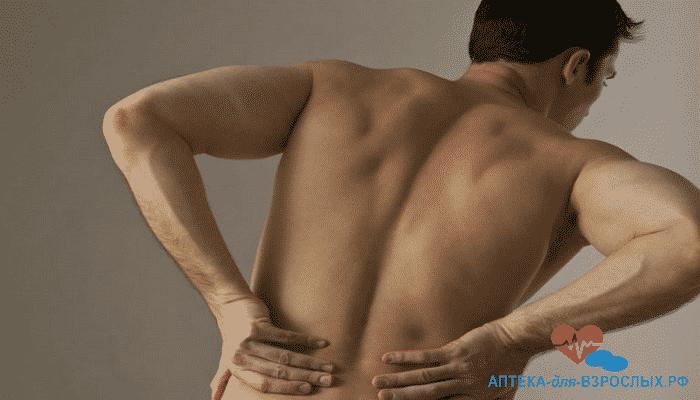 Мужчина держится руками за спину из-за передозировки препаратом