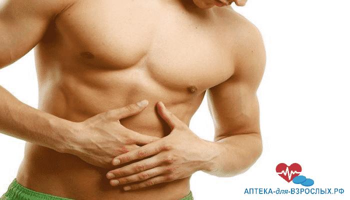 Мужчина держится за область живота из-за аллергической реакции на состав