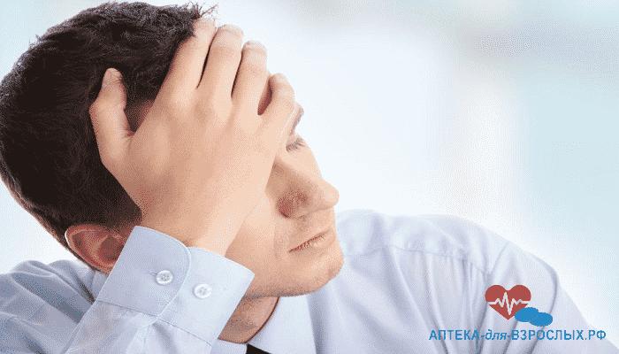 Мужчина держится рукой за голову из-за побочного эффекта