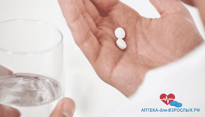 Мужчина держит в руках таблетки и стакан воды