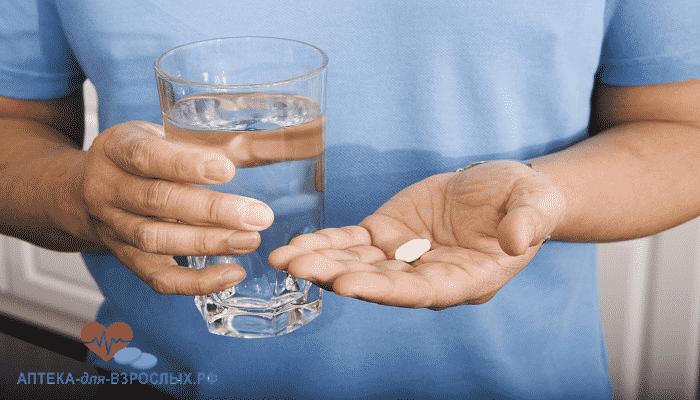Мужчина держит в руках таблетку и стакан воды
