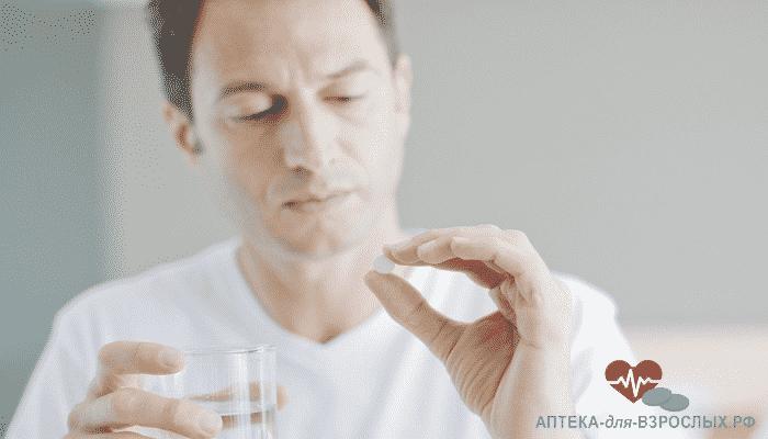 Мужчина держит таблетку для повышения потенции и стакан воды