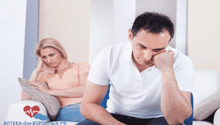 Мужчина задумался и сидит с женой на кровати