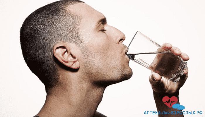 Мужчина запивает водой таблетку для повышения потенции