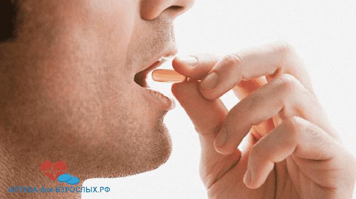 Мужчина подносит таблетку ко рту