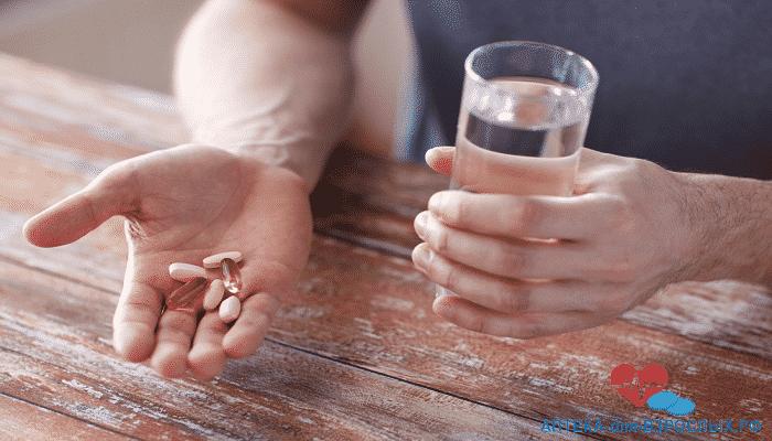 Мужчина со стаканом воды и капсулами в руках