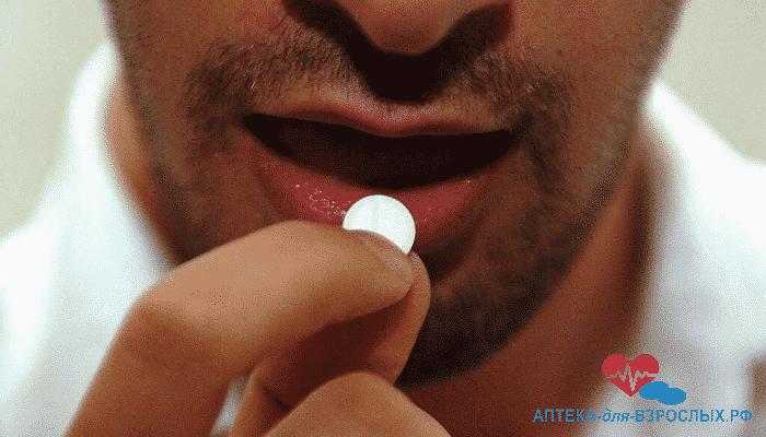 Небритый мужчина принимает таблетку для потенции
