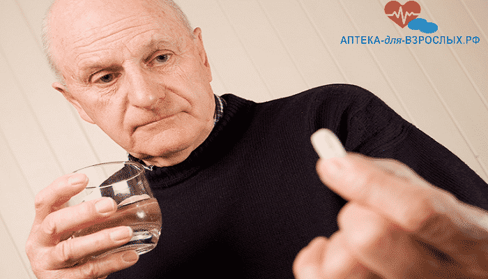 Пожилой мужчина держит в руке капсулу и стакан воды