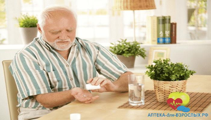 Пожилой мужчина принимает добавку к пище