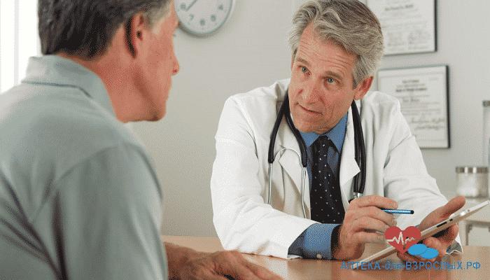 Седоволосый врач ведет беседу с пожилым пациентом